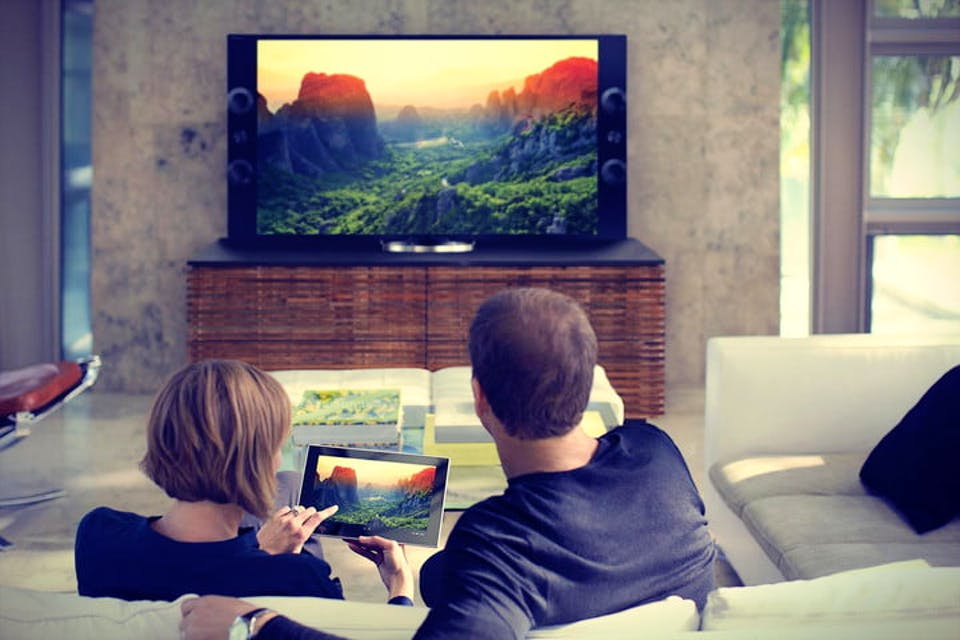 Couple with iPad connected to TV